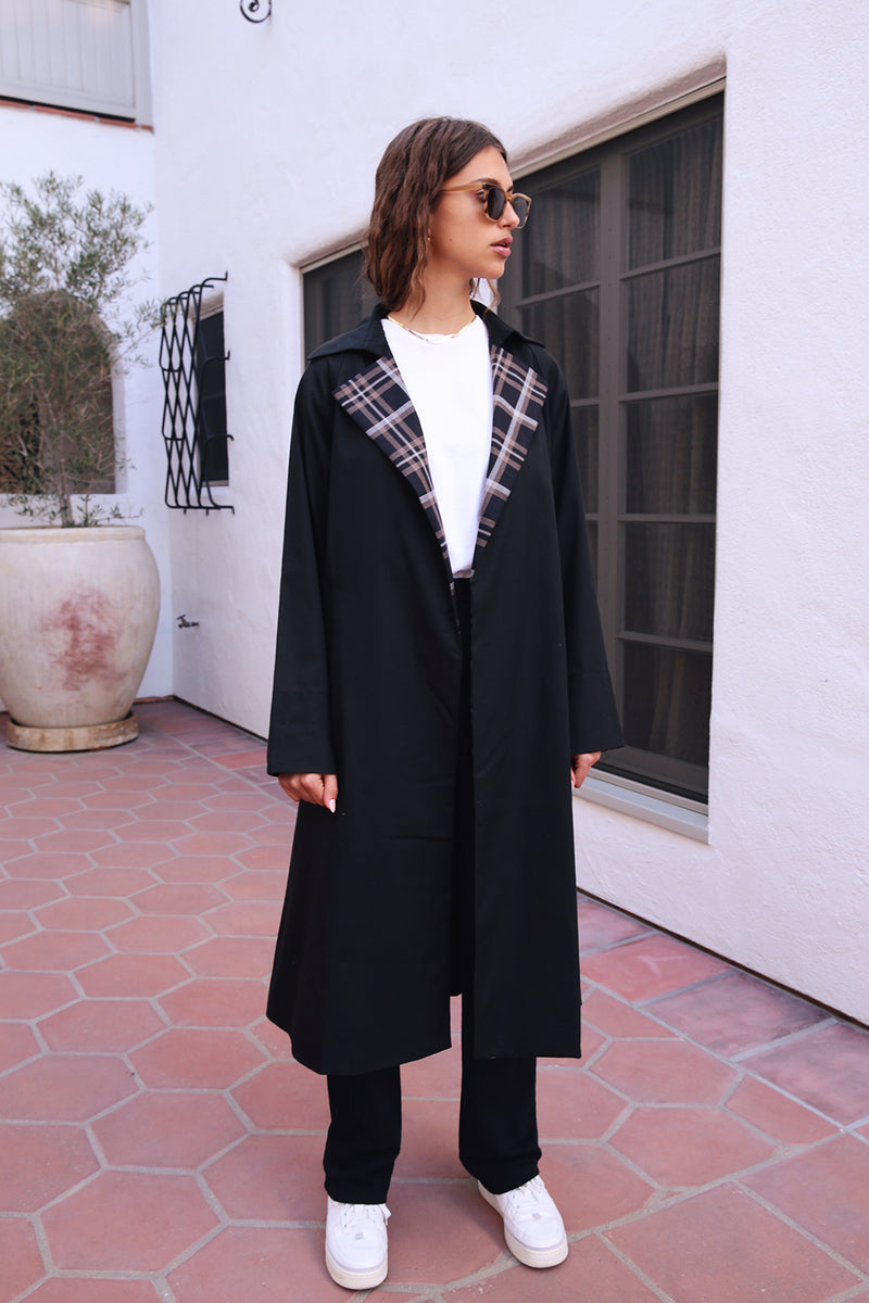 Model wearing the lady & the sailor Double Breasted Raglan Trench in Black Plaid.
