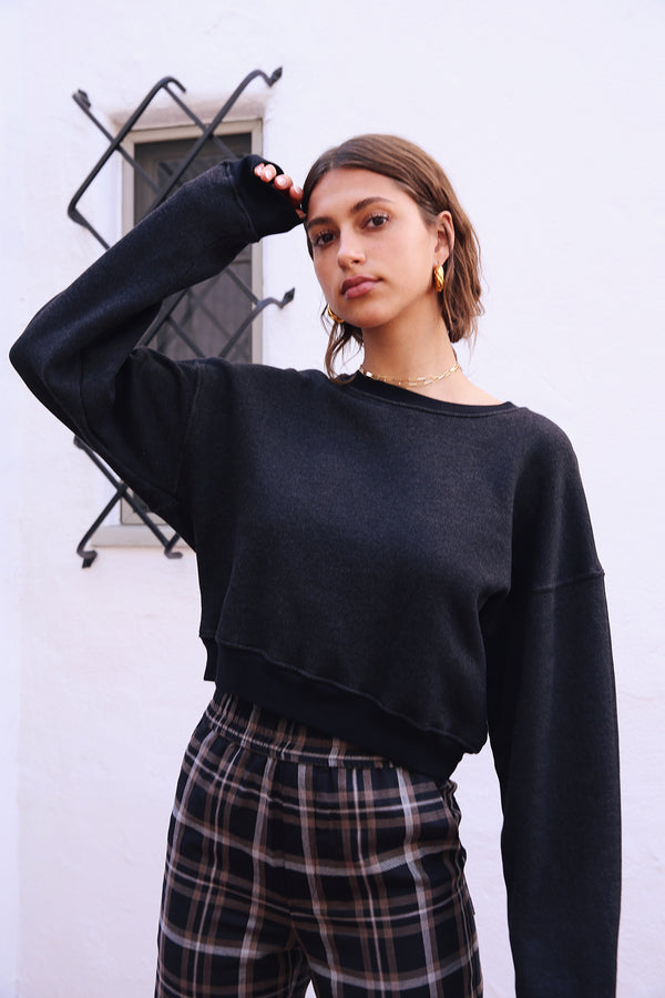 Model wearing the lady & the sailor Cropped Sweatshirt in Heathered Black Fleece.