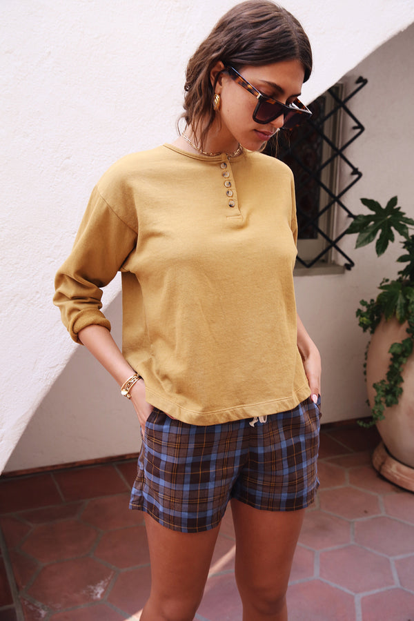 Model wearing the lady & the sailor Henley Sweatshirt in Marigold Organic Cotton.