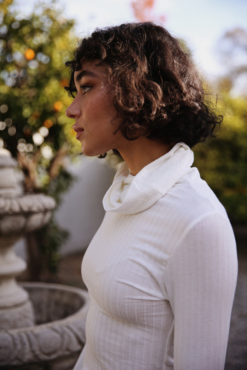 Model wearing the lady & the sailor Classic Turtleneck in White Pointelle.