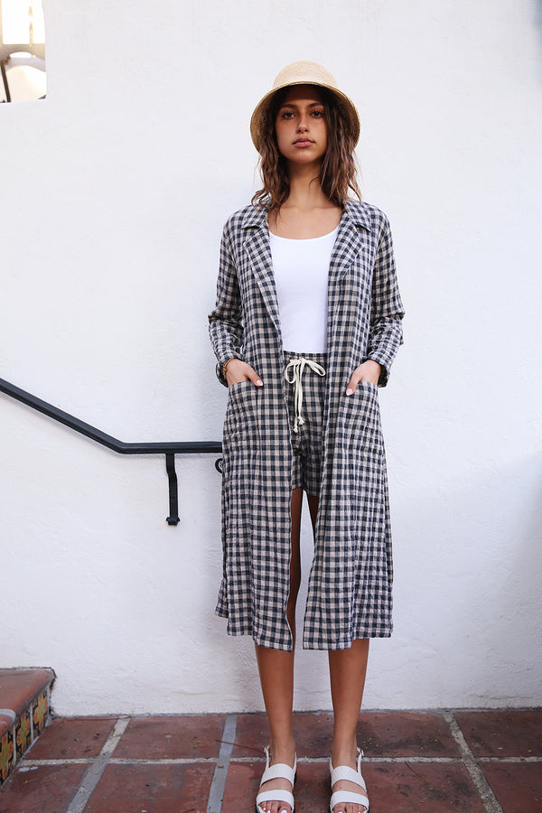 Model wearing the lady & the sailor Belted Coat in Taupe Gingham.