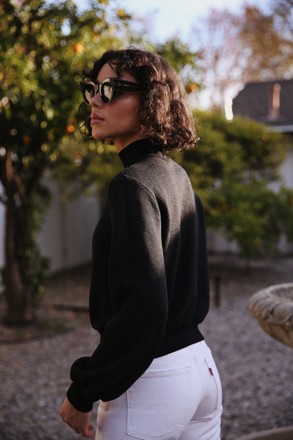 Model wearing the lady & the sailor Balloon Sleeve Mockneck in Heathered Black Fleece.