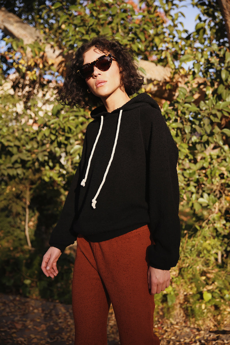 Model wearing the lady & the sailor Tomboy Hoodie in Black Boucle.