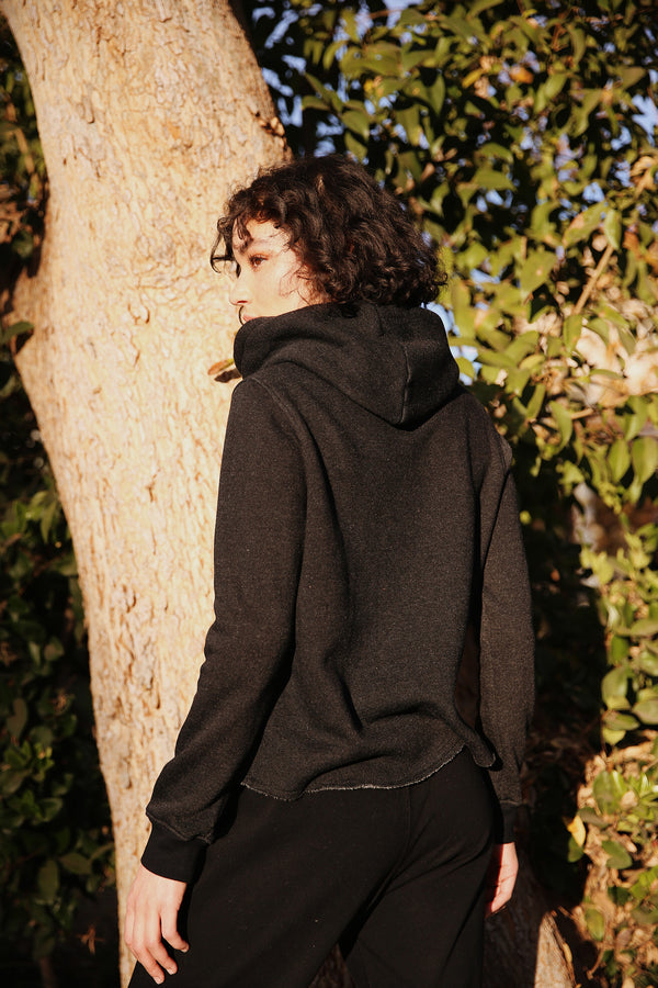 Model wearing the lady & the sailor Raw Bottom Hoodie in Heather Black Fleece.