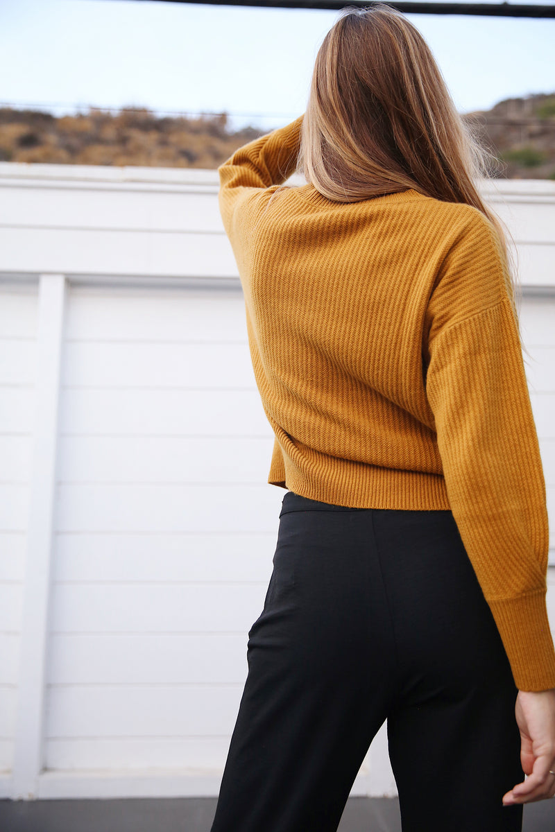 Model wearing the lady & the sailor Allude Ribbed Sweater in Mustard.