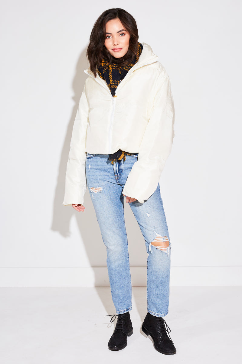Brunette model wearing Arch The Cropped Puffer Jacket in ivory.