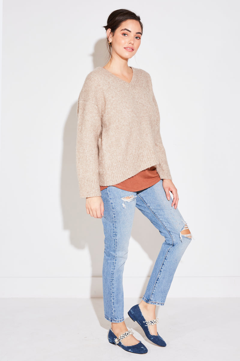 Brunette model wearing Arch The Relaxed V Neck Sweater in beige cashmere.