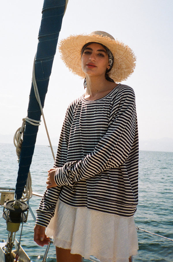 Model wearing navy striped sweatshirt, white mini skirt and straw hat.