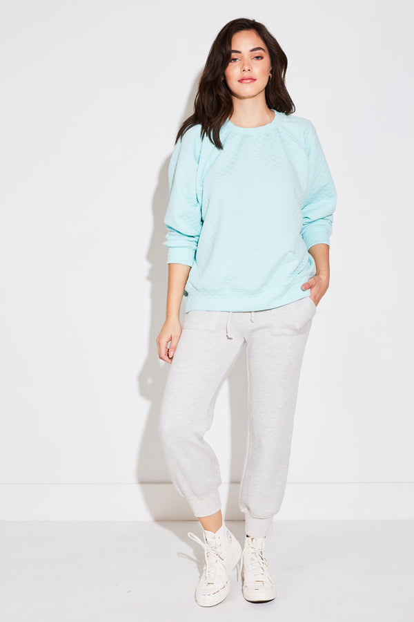 Model wearing the lady & the sailor Brentwood Sweatshirt in aqua quilted.