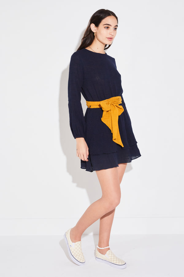 Model wearing the lady & the sailor Emelia Dress in navy/golden gauze.