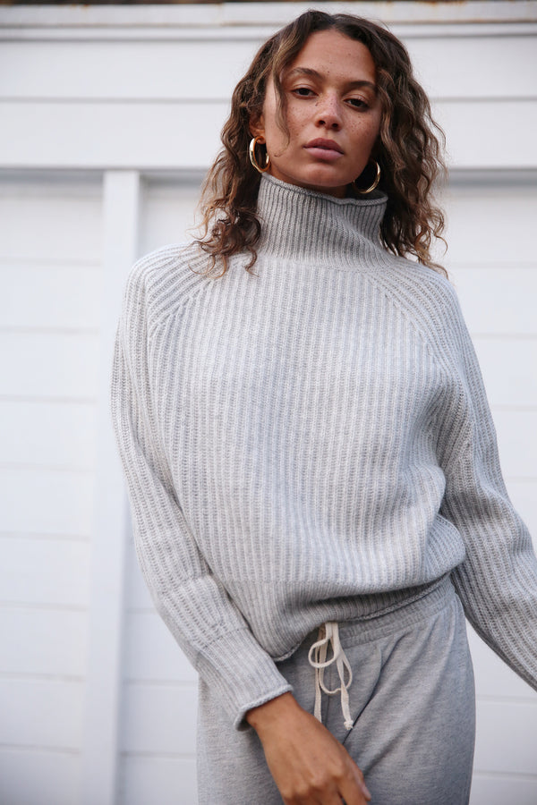 Model wearing the lady & the sailor Allude Turtleneck Sweater in Heather Grey.