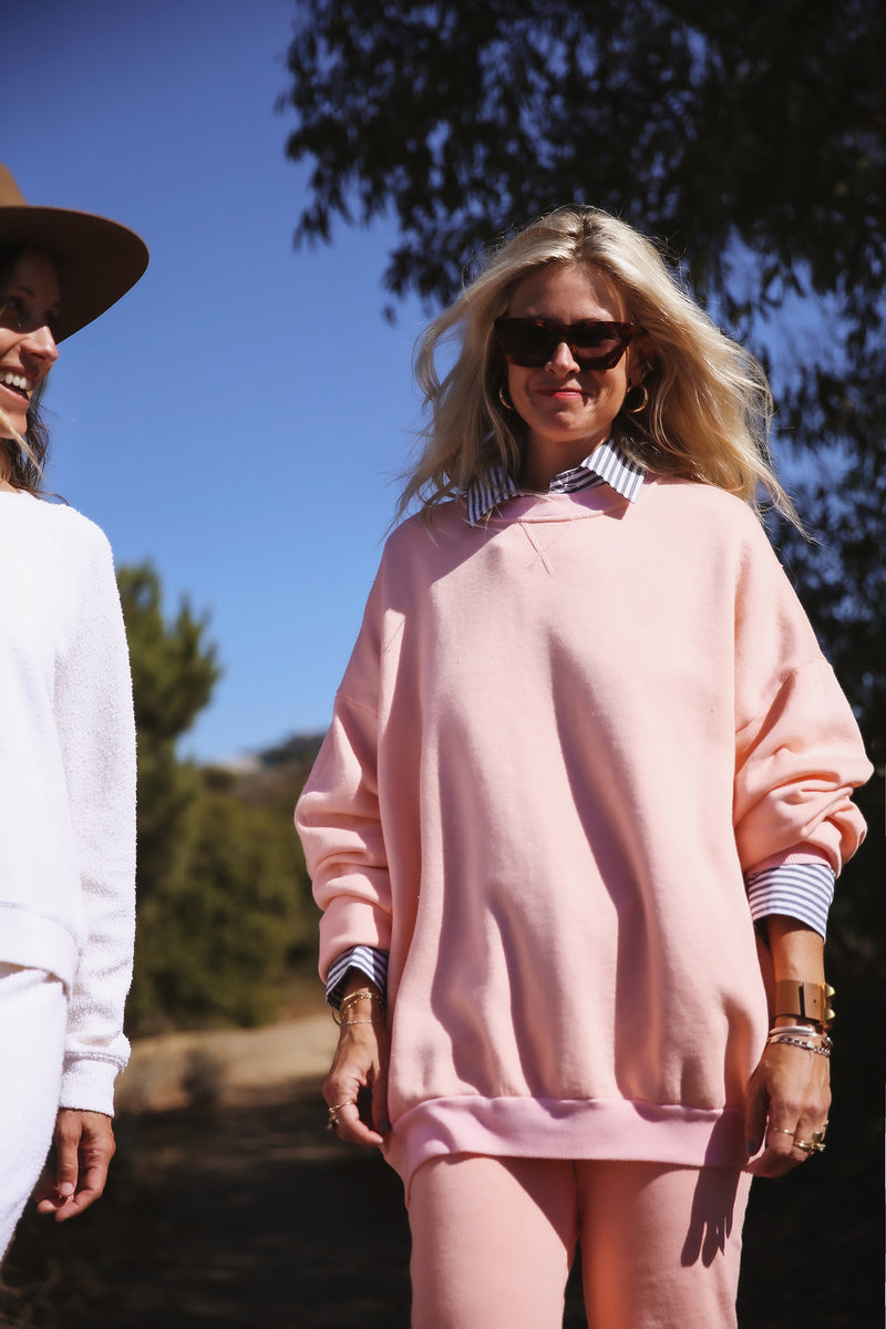 Model wearing the lady & the sailor Sandi Sweatshirt in Sunset Pink Fleece.