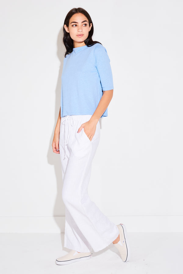 Model wearing the lady & the sailor High Waisted Pant in white linen.