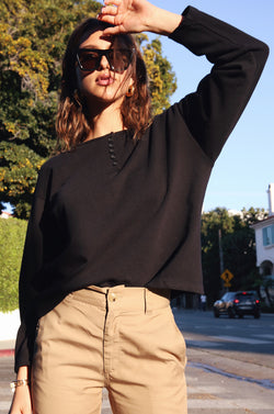Model wearing the lady & the sailor Henley Sweatshirt in Black Organic Cotton.