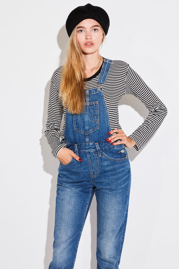 Blond model wearing Mature Ha Beret, Striped black and white long sleeve t-shirt, and Levi's Original Overalls in Bottom End.