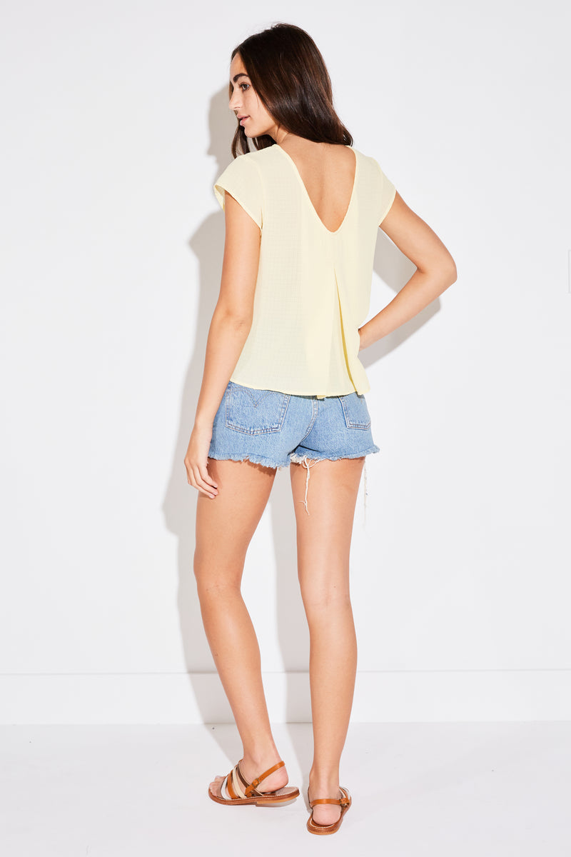 Model wearing the lady & the sailor Pleated Swing Tee in pale yellow french woven.