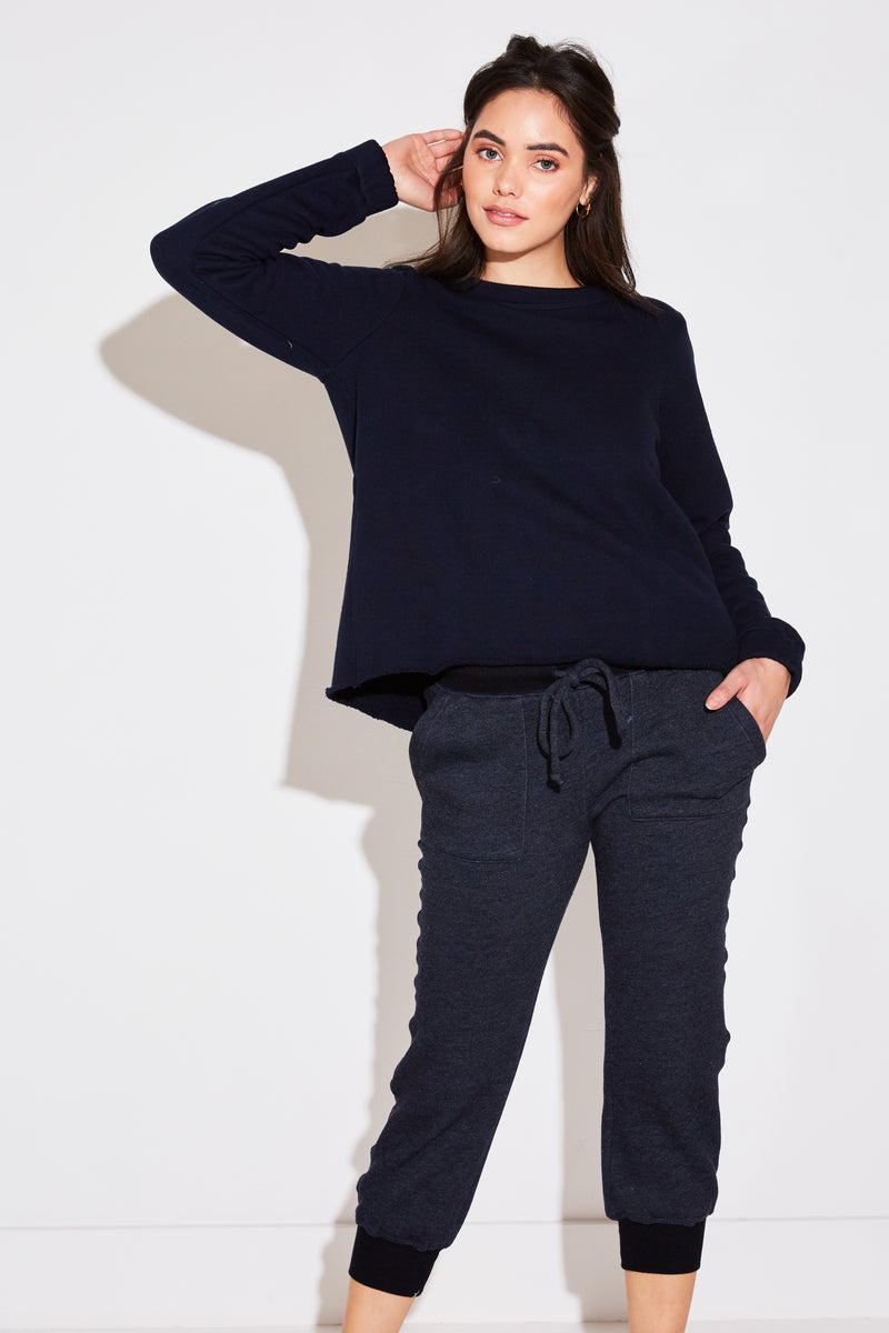 Model wearing the lady & the sailor Pleat Back Sweatshirt in navy french terry.