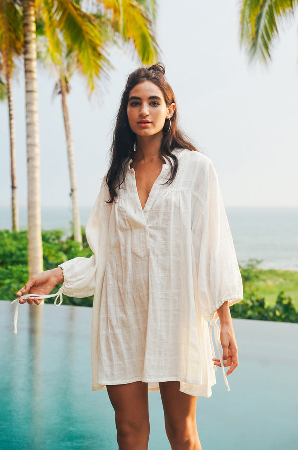Model standing by pool in white mini tunic dress