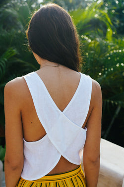 Model wearing the lady & the sailor Cross Back Tank in white linen.