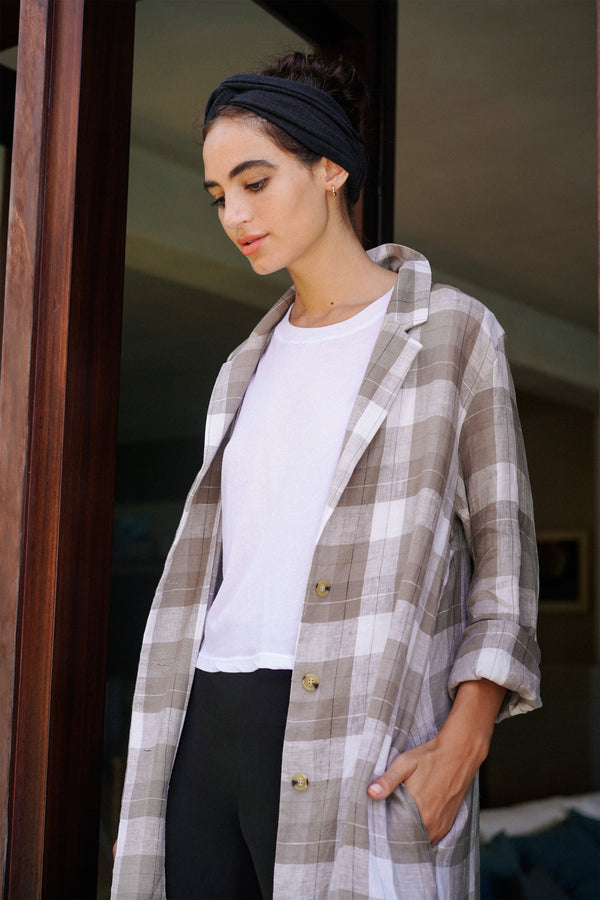 Model wearing beige plaid linen coat, white t-shirt and black turban headband.