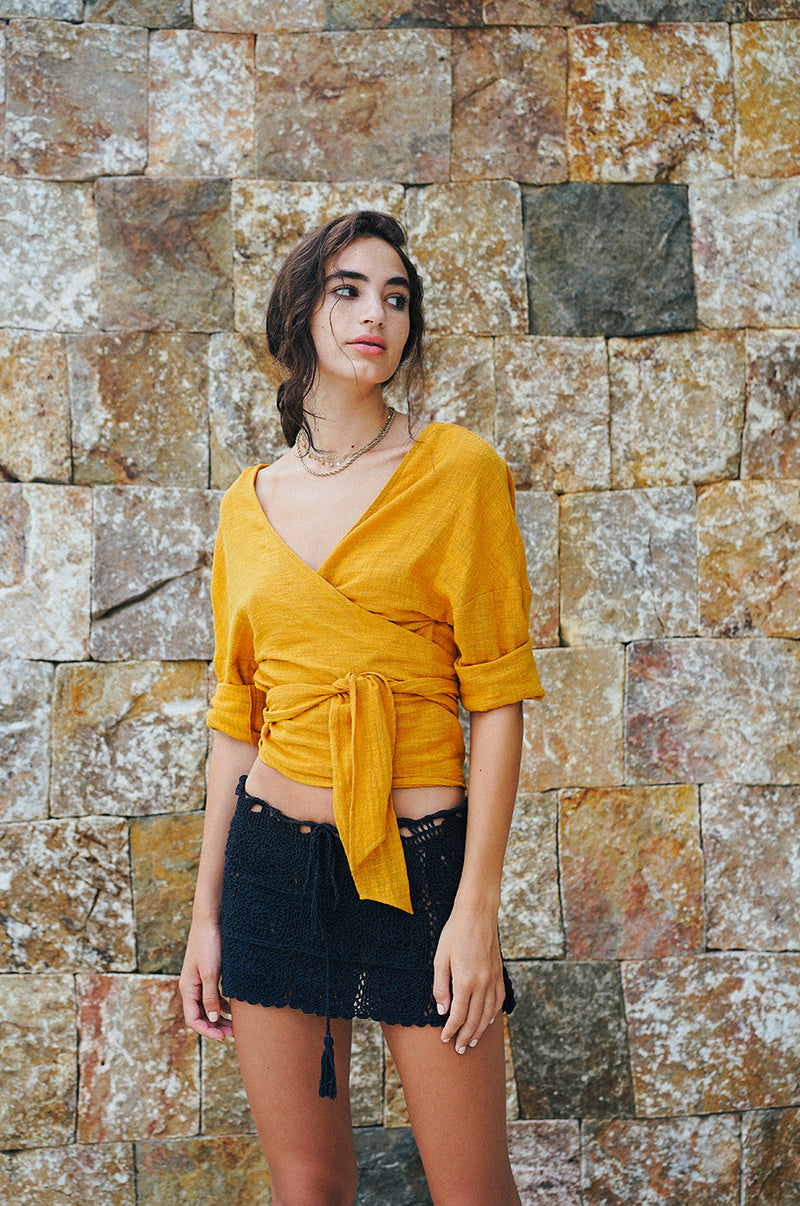 Model wearing the lady & the sailor Reversible Tie Blouse in golden gauze.