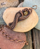 Woven Copper surrounds this Bronzite bead in this one of a kind handmade adjustable bracelet.