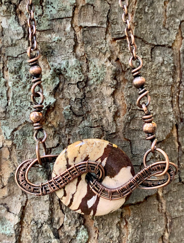 Brown Zebra Jasper Donut wrapped in handwoven copper to create this unique necklace with copper bead accents.