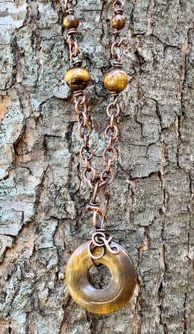 This necklace features a freeform wrapped Tiger Eye Bead on a copper chain with Tiger Eye Bead Accents.