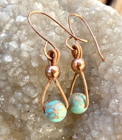These lightweight earrings feature light turquoise Impression Jasper hanging from tan leather with copper bead accents on handmade copper ear wires.