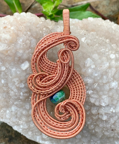 Layers of handwoven copper and copper coils surround a Lapis Chrysocolla Bead, creating a stunning intricate pendant.