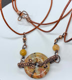 Copper wire wrapped Crazy Lace Agate Donut Necklace with Copper and Lace Agate bead accents on a leather cord.