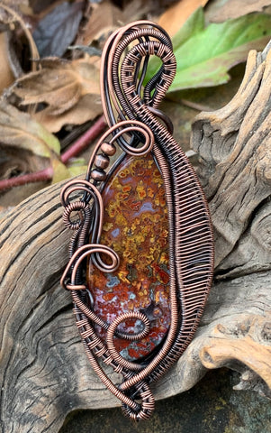 Colorful Red and Yellow Agate Pendant in layers of wire wrapped, curled and coiled copper.