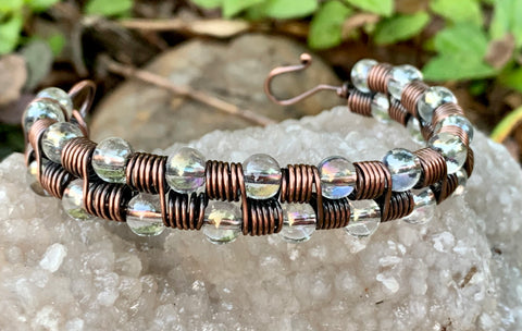 Adjustable iridescent glass bead and copper coils bracelet.