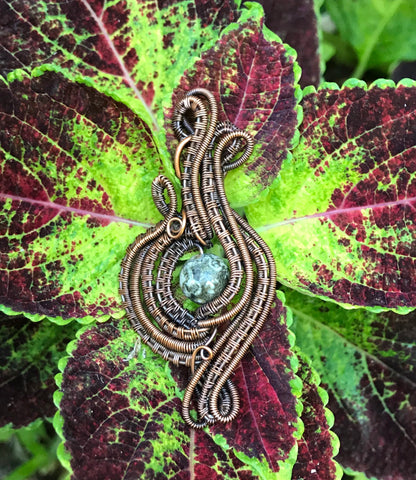 Wire wrapped Copper Pendant with handwoven and coiled copper layers with a Rhyolite Center.