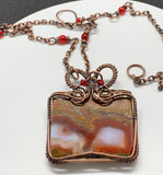 Polished Moroccan Seam Agate Slice Necklace wrapped in handwoven copper with Swarovski crystal accents and a copper chain with glass beads.