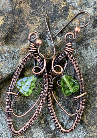 Wire wrapped Copper earrings with a green glass leaf accent on Niobium ear wires.