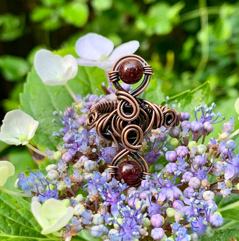 Handwoven copper and copper swirls accented with two African Garnet Beads in this lovely ring.