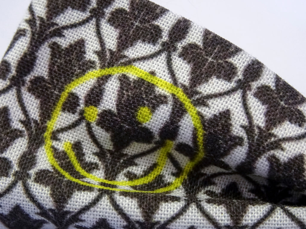 Detail on a Sherlock Wallpaper Inspired Pre-Tied Bow Tie. This is a white & black patterned bowtie with a yellow smiley face.