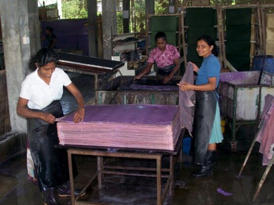 ladies making large sheets of handmade elephant dung paper