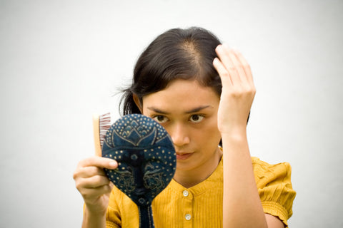 balding woman looking in mirror