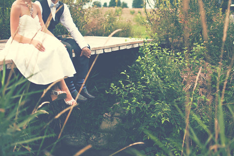 bride and groom sitting on bridge
