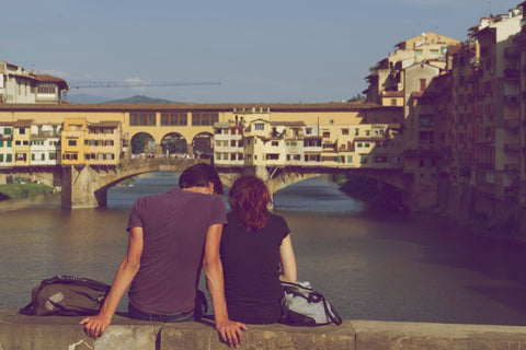 couple sitting together on bridge