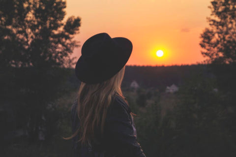 woman wearing hat in sunset