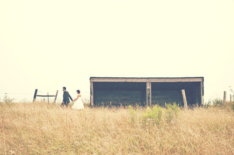 married couple walking in field