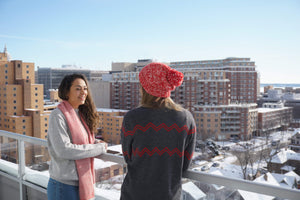 Girls talking outside during winter in red and white alpaca pom pom beanie