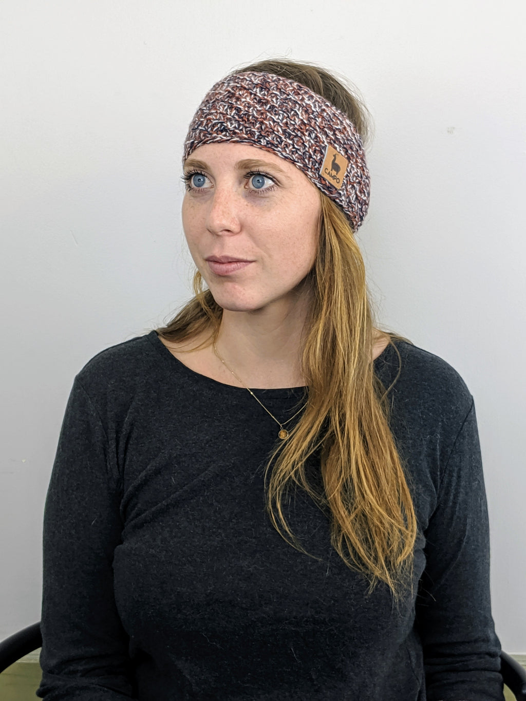 Girl wearing orange, blue, and white alpaca headband
