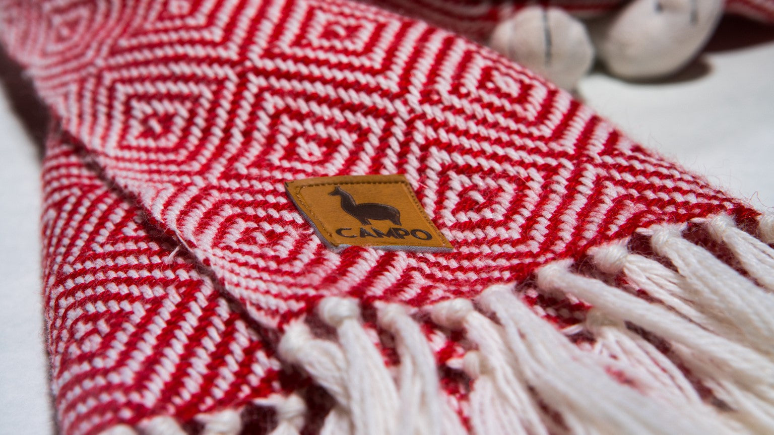 Close up of campo logo on Alpaca Woven Scarf in Red Diamond