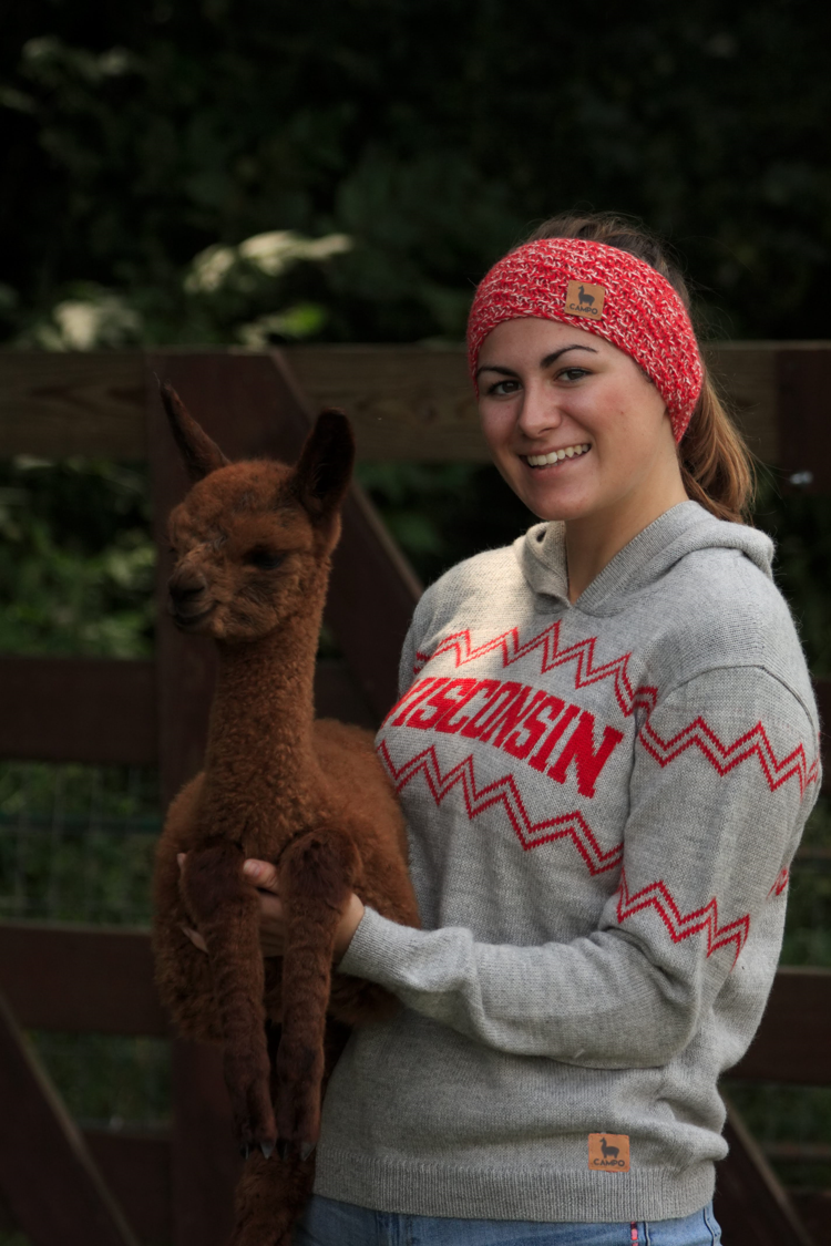 Girl holding alpaca wearing red and white alpaca headband and Wisconsin hooded alpaca sweater