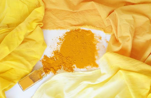 fabrics with yellow color natural dye with light and dark shade with dye powder in the center