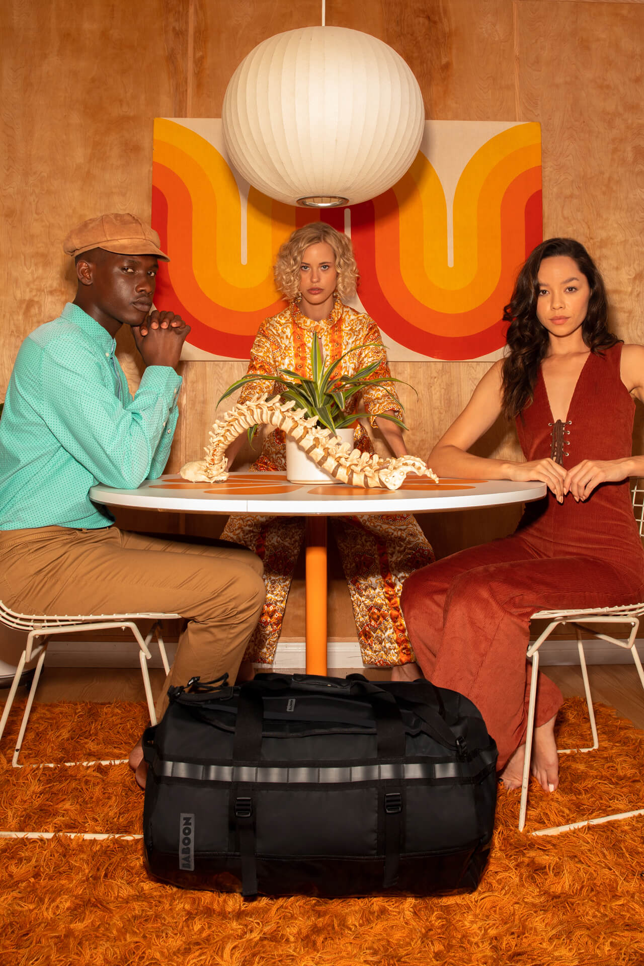 edge to edge image of 3 people sitting at a table with black BABOON bag on the floor